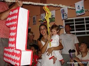 Barbara en Kyra slaan op de piñata, Roland kijkt rechtsonder in de hoek toe