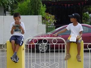 Tariq en Luchiano lezen op het hek